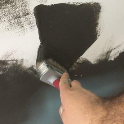 Målar väggen med pensel